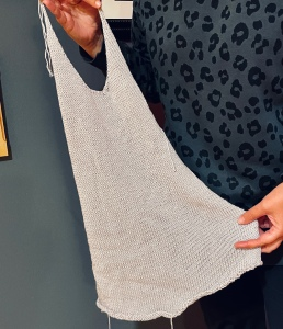 one half of a grey knitted top